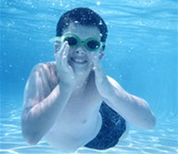 A boy with goggles swims underwater